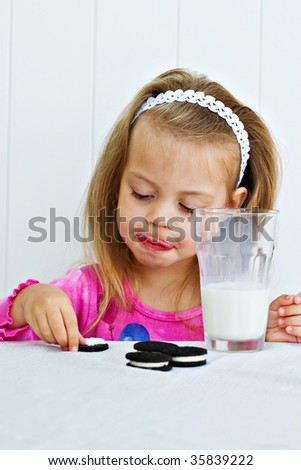 Little girl eating creme filled cookies while drinking a glass of milk.
