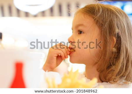 Little girl eating fast food french fries and drink coke cola