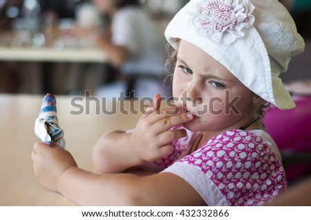 Little girl eating ice cream in cafe on the beach - stock photo