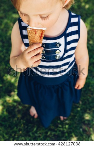 Little girl eating ice cream in nature - stock photo