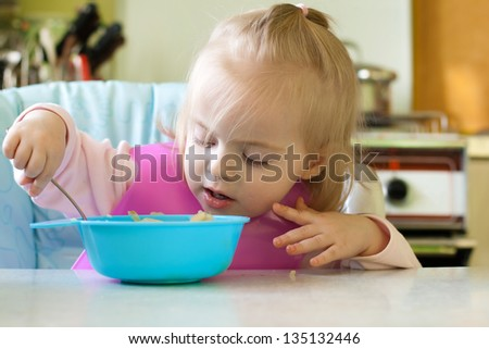 Little girl eating in the kitchen