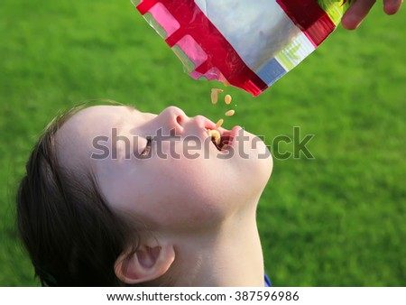Little girl eating pine nuts - stock photo