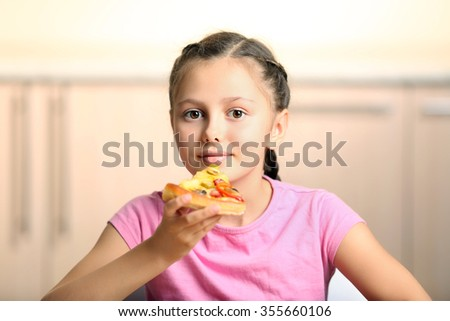 Little girl eating pizza at home - stock photo