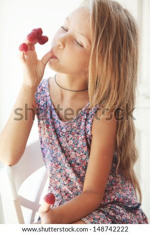 Little girl eating raspberries on her fingers - stock photo