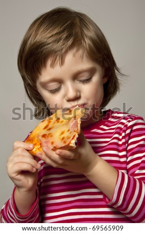 little girl eating slice of pizza - stock photo