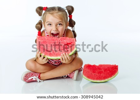 Little girl eating two slices of watermelon, studio shoot - stock photo