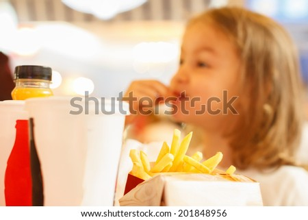 Little girl eating unhealthy fast food french fries and drink coke cola - stock photo