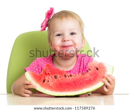 Little girl eating watermelon at table - stock photo