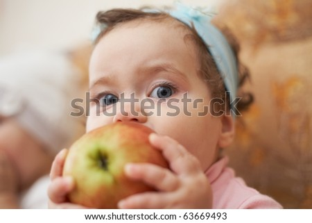little girl eats an apple - stock photo