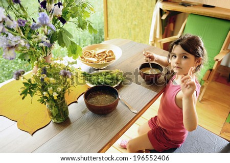 Little girl eats soup. morning in  kitchen - stock photo