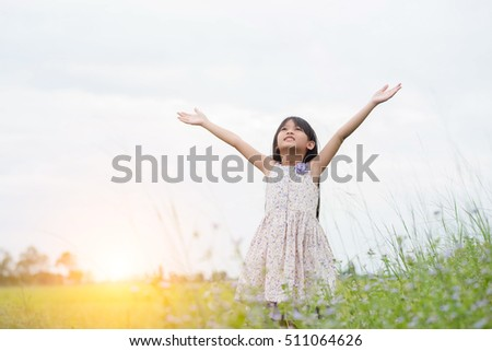 Little girl enjoy with nature on meadow field.