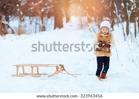 Little girl enjoying a day out playing in the winter forest - stock photo