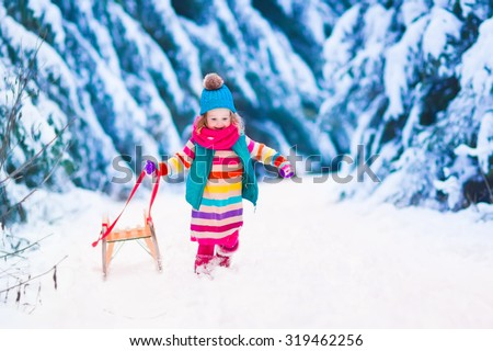 Little girl enjoying a sleigh ride. Child sledding. Toddler kid riding a sledge. Children play outdoors in snow. Kids sled in the Alps mountains in winter. Outdoor fun for family Christmas vacation. - stock photo