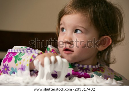Little girl enjoying playing with foamy cream - stock photo