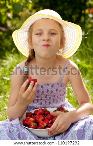 Little girl enjoys a ripe red strawberry - stock photo