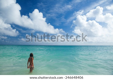 Little girl enjoys summer day at the tropical beach. - stock photo
