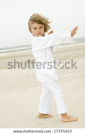 Little girl exercising on the beach