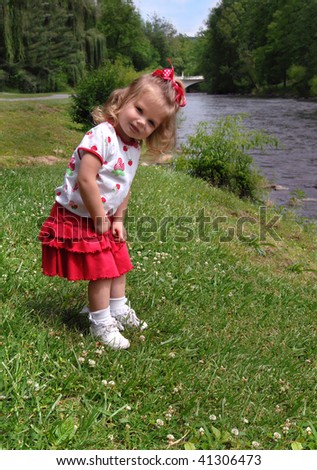 Little girl explores the banks of the Doe River in Tennessee.  She is bent over looking down river. - stock photo