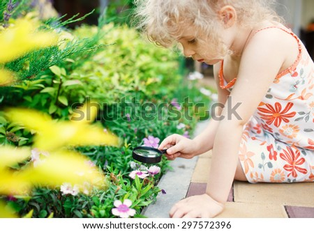 Little girl exploring nature with a magnifying glass - stock photo