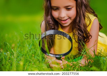 Little girl exploring through magnifying glass - stock photo