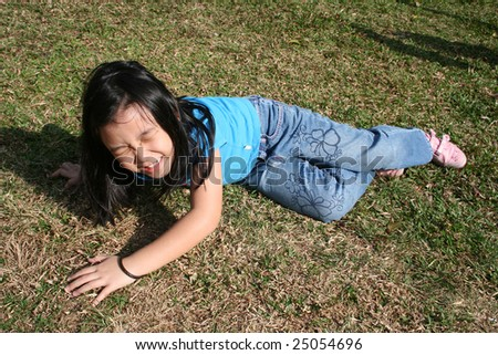 Little girl falling off at the park on sunny day - stock photo