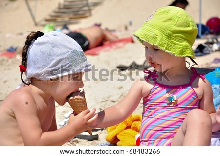 Little girl feeding her friend with ice-cream on the beach - stock photo