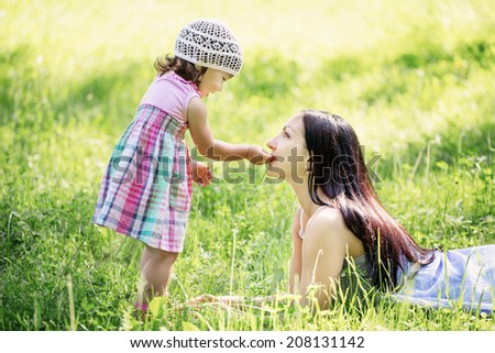 little girl feeding her mother a blade of grass - stock photo