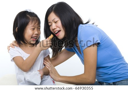 Little girl feeding her mum cone ice-cream. - stock photo
