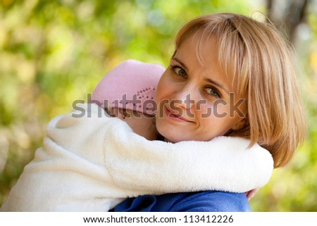 Little girl fell asleep in the arms of mother - stock photo