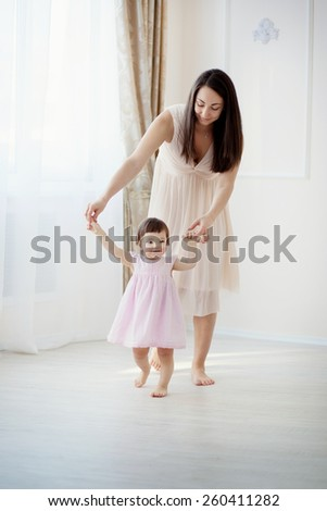 little girl first steps with the help of mom - stock photo