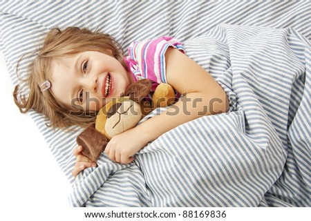 little girl four years old in the bed with toy - stock photo