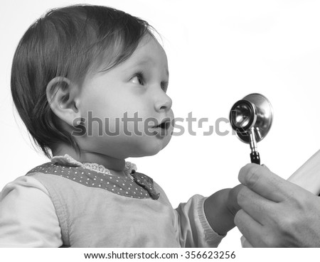 Little girl gets to know her medical doctor - stock photo