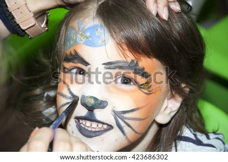 Little girl getting her face painted like a tiger by face painting artist - stock photo