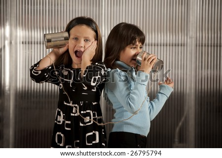 Little girl getting shocking message from friend on tin can phone - stock photo
