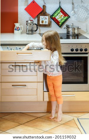 Little girl getting tableware from table case before dinner - stock photo