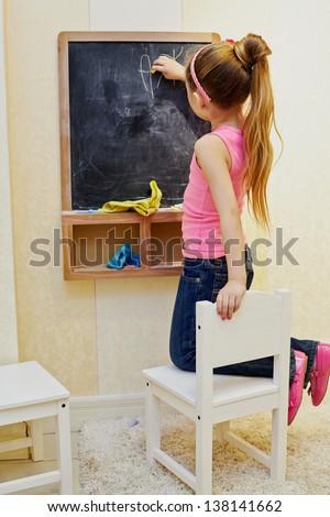 Little girl girl writes with chalk on blackboard, kneeling on chair - stock photo