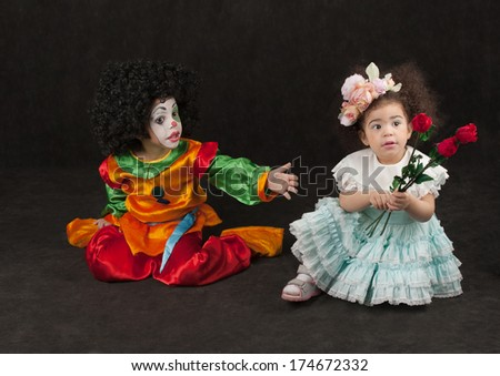 little girl gives flowers to the boy - clown, black  - stock photo