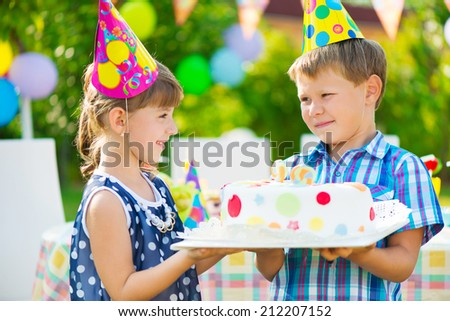 Little girl giving a birthday cake to her friend - stock photo