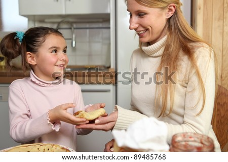 Little girl giving her mother a crepe - stock photo