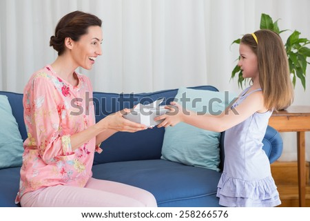 Little girl giving her mother a gift at home in the living room - stock photo