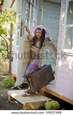 Little girl going out of her wood house for playtime. - stock photo