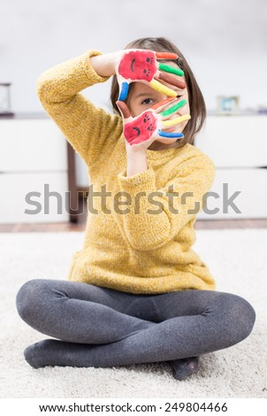 Little girl have funny time with painted hand - stock photo