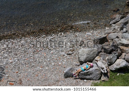 little girl having a sunbath on a big rock near the water of the Lago Maggiore in Italy