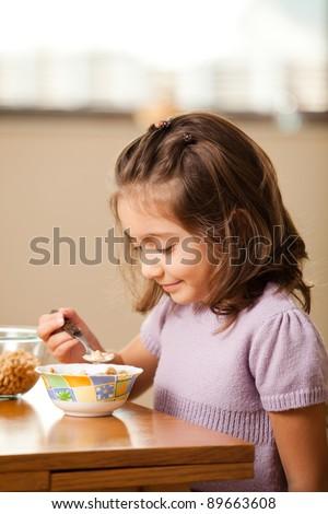 little girl having breakfast: cereals with milk - stock photo