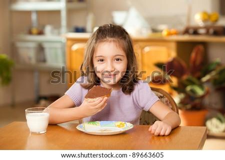 little girl having breakfast: eating chocolate cream on a slice of bread - stock photo