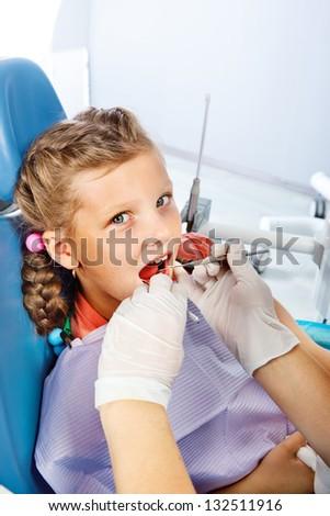 Little girl having dental checkup - stock photo
