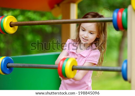 Little girl having fun at a playground - stock photo