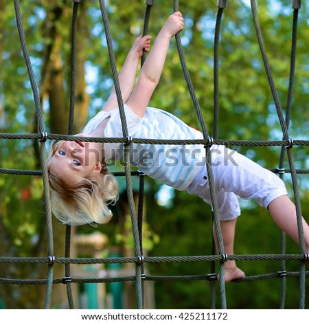 Little girl having fun at playground. Happy cute child, blond sportive toddler girl in casual outfit, playing in the park on a sunny day. Leisure outdoors activity with children. - stock photo