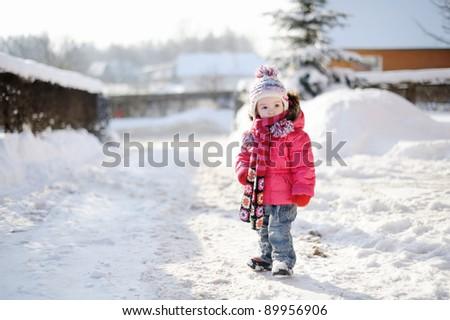 Little girl having fun at winter day - stock photo