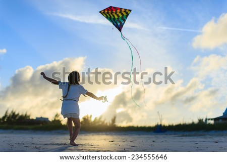 Little girl having fun flying a kite at beach during sunset - stock photo